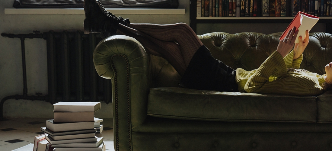 woman in tights laying on chair reading book in library
