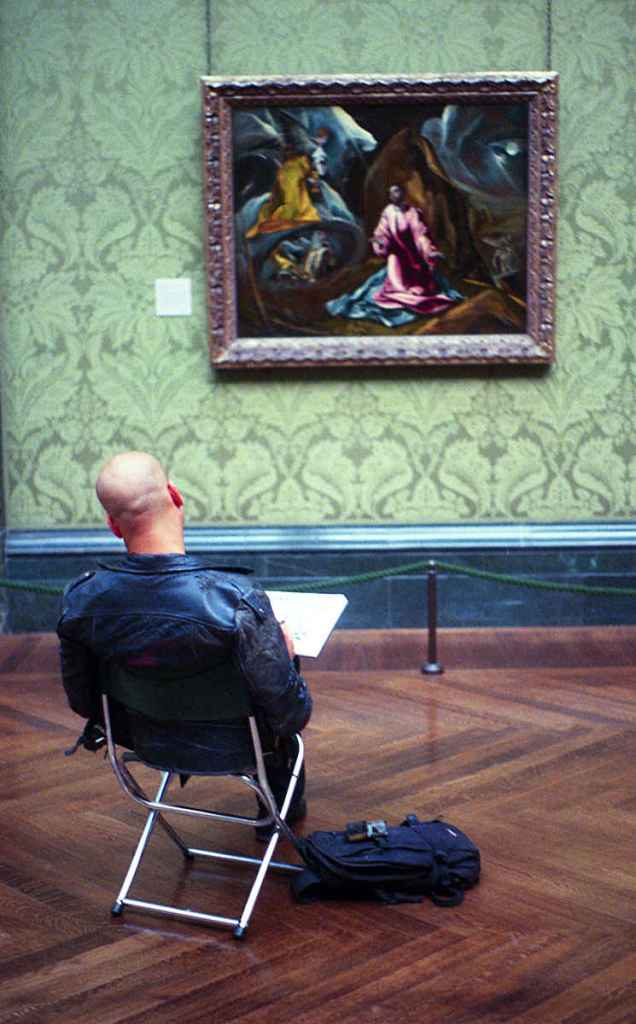 Man artist in gallery copying studying old master artwork in seat
