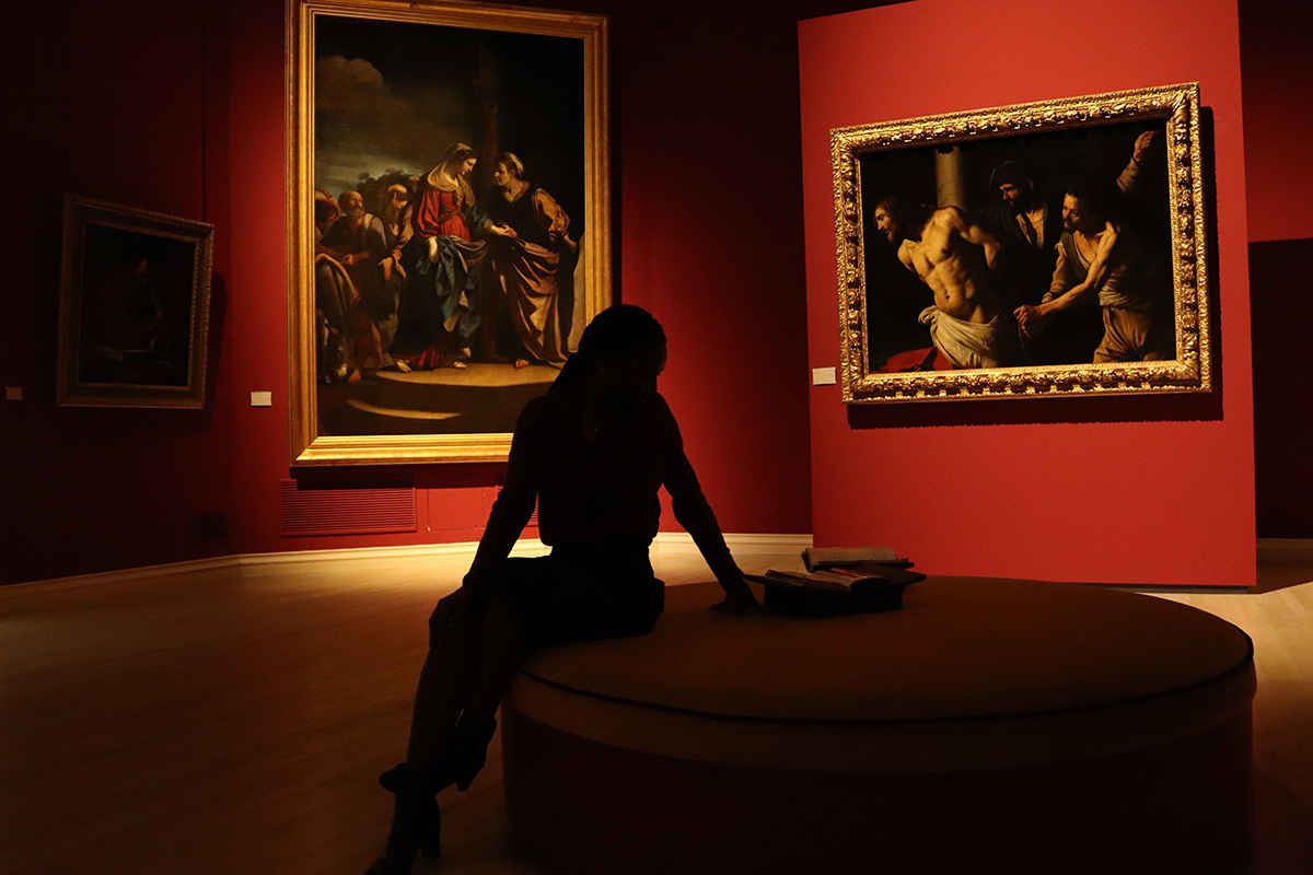 Woman sitting in art gallery looking at art paintings renaissance red walls photo